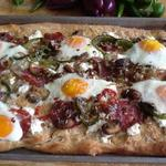 Breakfast pizza with eggs and fresh greens